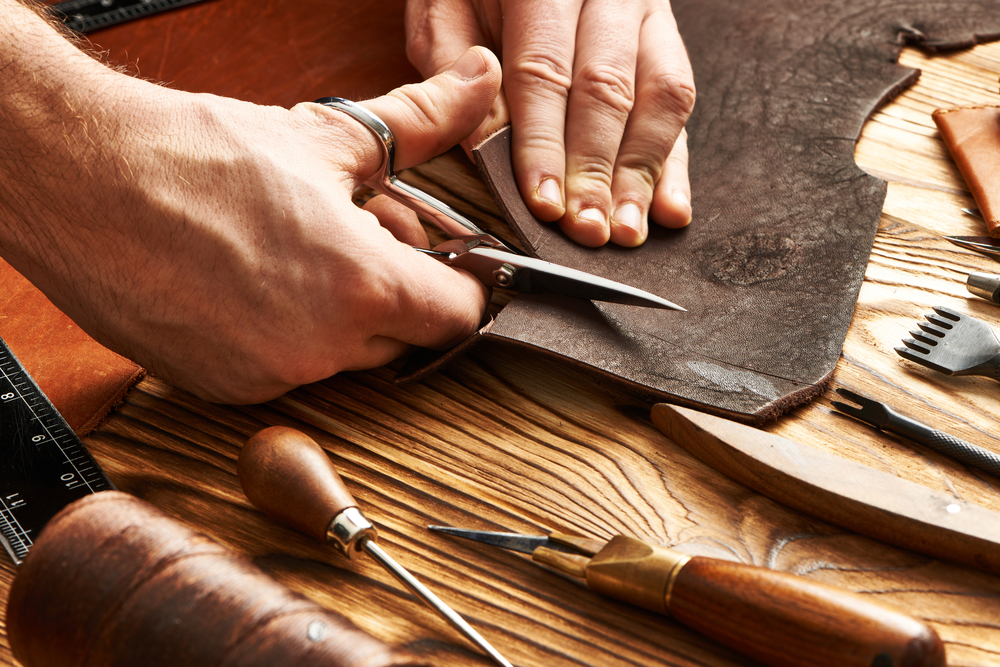 Man working with different types of leather using crafting DIY tools