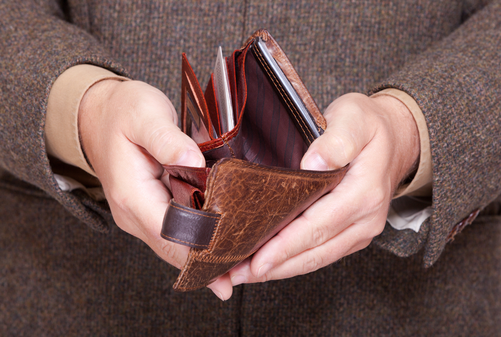 Broke businessman showing brown leather empty wallet. Business concept- finance and poor economy, how to clean leather wallet